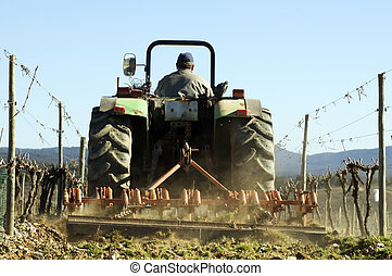 Tractor ploughing field - Farmer using a tractor ploughing a...
