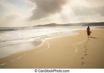 Towards the light - Young woman walk on an empty wild beach...