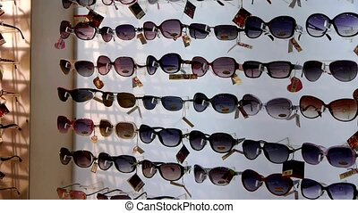 entire wall of sunglasses at the mall.