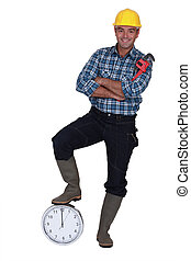 Tradesman with his foot propped on a clock