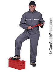 Tradesman with his foot propped on a toolbox