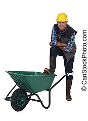 Tradesman with his foot propped on a wheelbarrow
