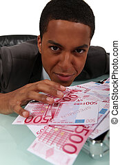 Young businessman with a pile of cash