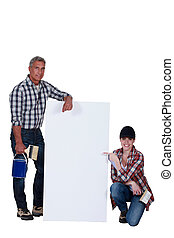 female and male painter presenting an ad board