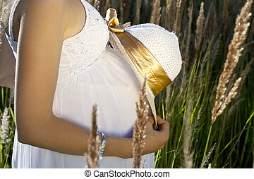 Pregnant  belly with the hat in sunbeams