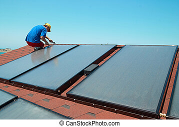 Worker installs solar panels - Worker solar water heating...