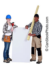 craftswoman and craftsman holding an ad board