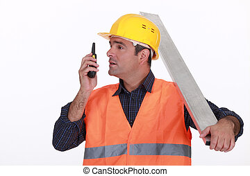 Labourer speaking into a walkie-talkie