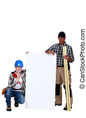 Plumber and carpenter holding white board
