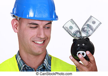 Construction worker with money in a piggy bank