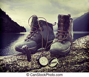 Hiking boots on tree trunk near lake - Hiking boots with...