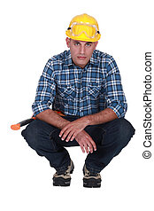Squatting tradesman with a piercing stare