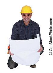 Smiling tradesman looking at a blueprint