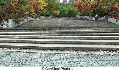 Pan on stairs in autumn Prague park with cloudy sky