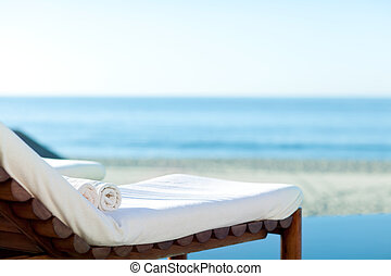 sunbed on a beach - empty sunbed with wrapped towels on a...
