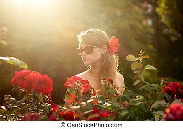 young woman in flower garden smelling red roses #1