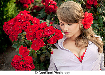 young woman in flower garden smelling red roses