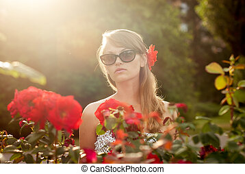 young woman in flower garden smelling red roses #3