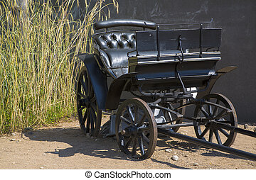 Black wagon without horses is abandoned by driver