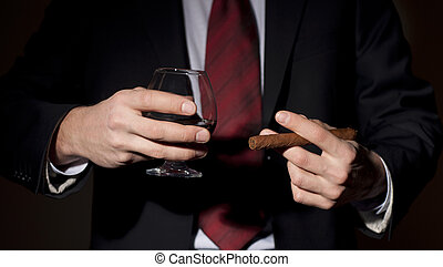 rich person, holds a cigar and whisky