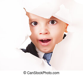 Yawning kid looks through a hole in white paper