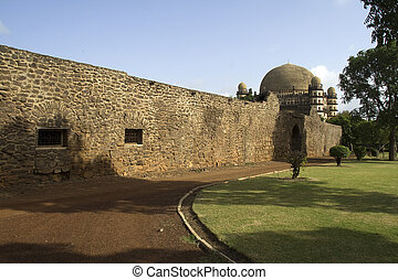 Gol Gumbaz behind barricade - Lengthy stone wall partially...