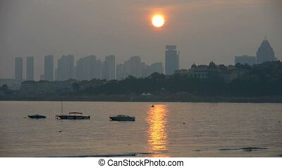 Dusk waterfront.Ship boat on the sea,horizon is high-rise...