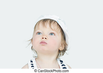 curious expression of little girl in cap