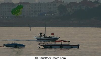 Clipper boat dragging paragliding,horizon is high-rise...