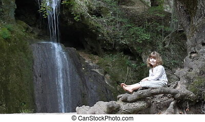 little girl sitting near waterfall