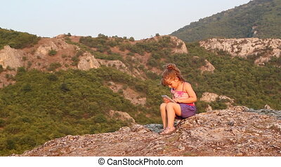 little girl sitting on a mountain