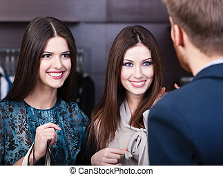 Two girls smiles at shop assistant - Two young women smiles...