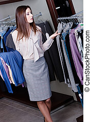 Choosing clothes at the store - Young woman chooses clothes...