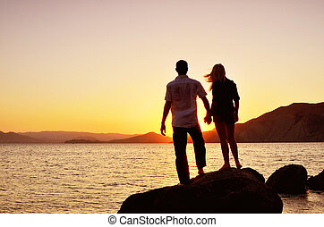 couple watching the sun by the sea while standing on a rock