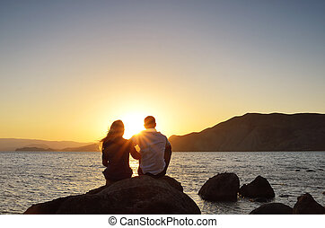 Loving couple looking at the sun - Young couple sitting on a...