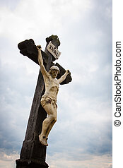 Old statue of Christ by a countryside road against cloudy...
