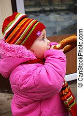 Little girl eats a bagel