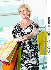 Payment - Portrait of middle aged woman with paperbags...