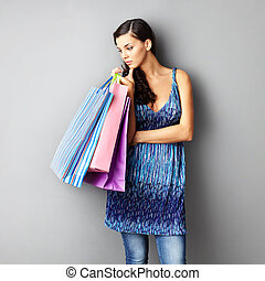 Pensive shopper - Portrait of young brunette with paperbags...