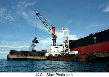 coal is being loaded onto tankers with a crane