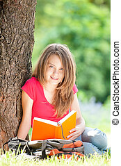 happy student girl reading book - beautiful and happy young...