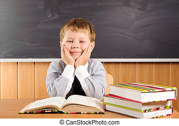 Cute boy with books at the desk