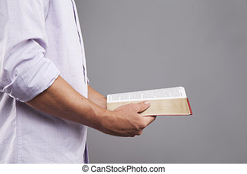 Profile of Hands holding Bible - A man stands indoors...