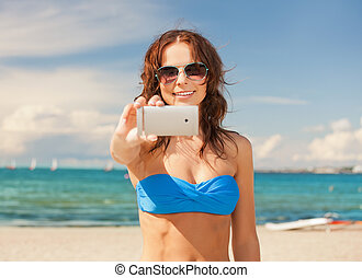 happy woman with phone on the beach - picture of happy woman...