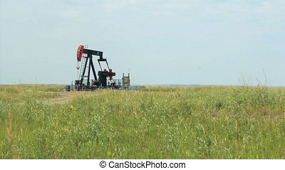 Oil Pump In Alberta - A lonely oil pump works tirelessly on...