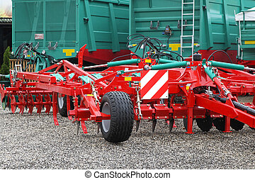 Disc harrow - Red disc harrow and green trailers at farm