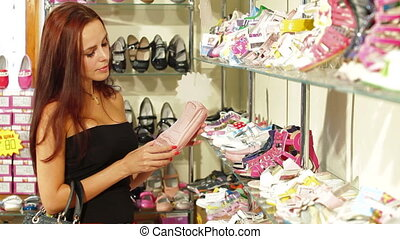 Woman Choosing Footwear - Young Woman Choosing Footwear in...