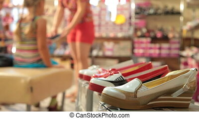 Children's Shoe Store - Mother and daughter choosing shoes...