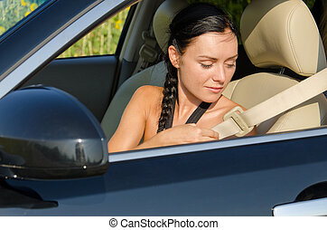 Woman putting on her seatbelt - Woman sitting in a car...