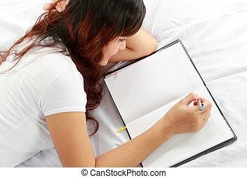 girl writing book on the bed - Closeup portrait of a relaxed...